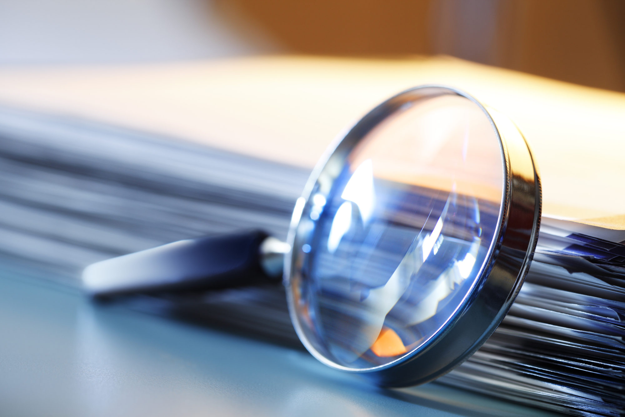 Magnifying Glass Leaning Against Stack Of Papers